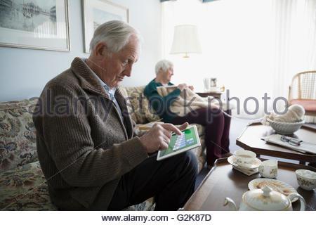 Senior couple jouer solitaire sur tablette numérique et de tricot dans la salle de séjour Banque D'Images