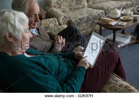 Vous jouez à Sudoku Senior couple on digital tablet Banque D'Images