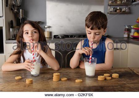 Petit garçon et fille assise à la table de cuisine faire des bulles dans un verre de lait Banque D'Images