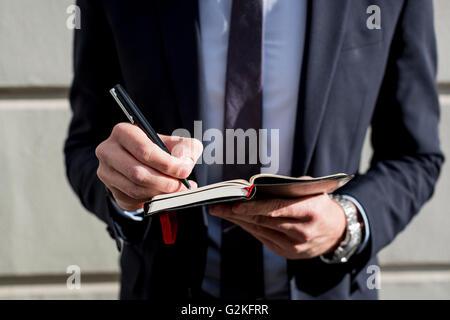 Businessman outdoors écrit dans journal Banque D'Images