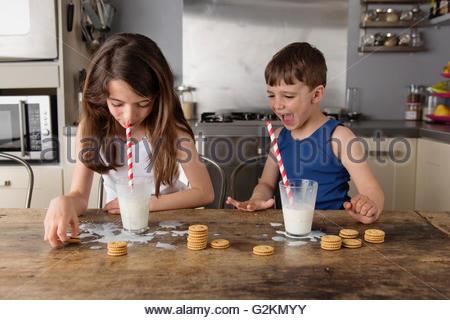 Petite fille assise faisant des bulles dans un verre de lait tout en regardant son frère Banque D'Images
