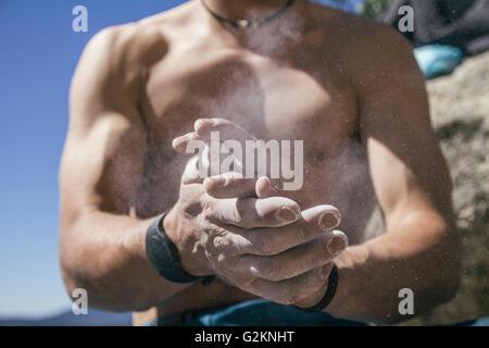 Revêtement grimpeur torse nu les mains dans la craie en poudre le magnésium Banque D'Images