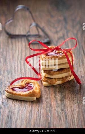 Une pile de biscuits avec de la confiture sur une table rustique en bois. Banque D'Images