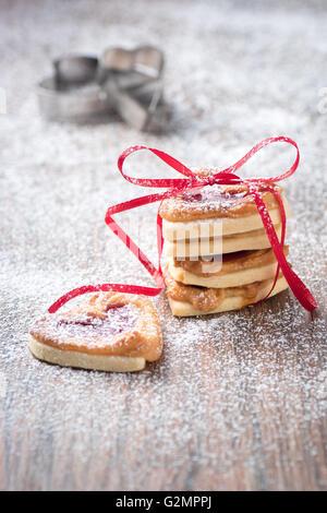 Les cookies de sucre glace rempli avec de la confiture un emporte-pièce à l'arrière-plan. Banque D'Images