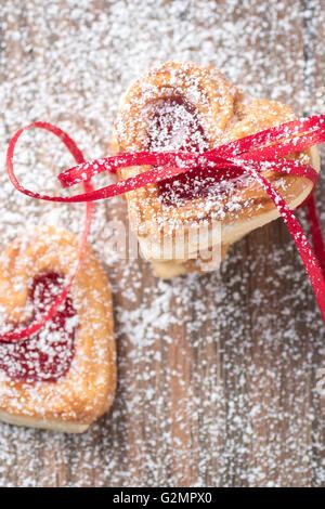 Coeur rempli de confiture cookies avec ruban et sucre glace libre. Banque D'Images