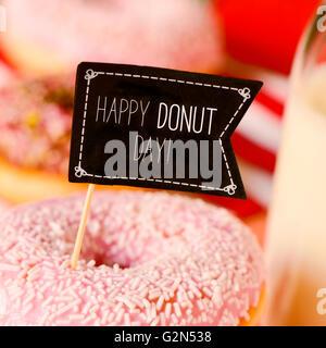 Libre d'une pancarte en forme de drapeau noir avec le texte heureux jour donut dans un appétissant donut recouvert Banque D'Images