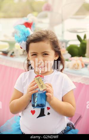 Cute girl de boire la potion 'Drink Me', Alice au pays des merveilles thème de partie de thé tonifiant, Banque D'Images