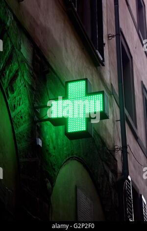 Un néon-vert signe en forme de croix dans les rues de Florence, en Italie. Le signe d'une pharmacie moderne contrastant Banque D'Images