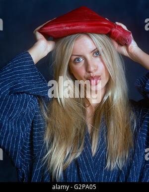 Zoe Mcconnal poussant sa langue dehors avec une bouteille d'eau chaude sur la tête. Banque D'Images