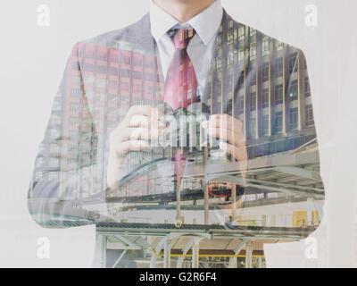 Double exposition de l'homme d'affaires en costume avec gratte-ciel sur l'arrière-plan Banque D'Images