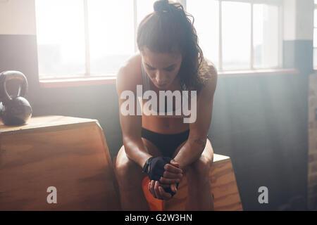 ... Jeune femme assise sur une boîte à gym après son entraînement et à la  recherche vers 83abab7c4bf