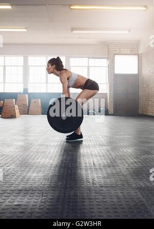 Vue de côté femme remise en forme faire de l'exercice avec un poids lourd dans la salle de sport. La femme pratiquant Banque D'Images