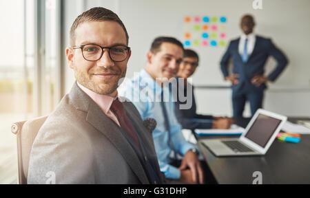 Beau barbu portant costume et cravate avec trois collègues de travail en réunion à la table de conférence en face Banque D'Images