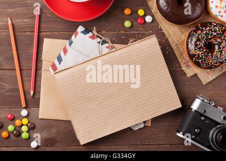 Le bloc-notes, des beignes et du café sur la table en bois. Top View with copy space