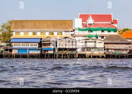 Maisons colorées sur pilotis sur les rives de la rivière Chao Praya, à Bangkok, Thaïlande Banque D'Images