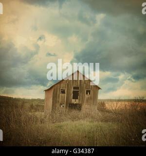Une vieille ferme abandonnée house se trouve dans le pays avec les nuages effrayant dans un champ pour une destruction Banque D'Images