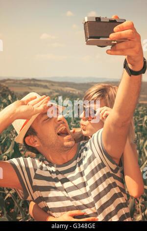 Jeune couple dans l'amour en tenant en selfies nature avec appareil photo rétro Banque D'Images