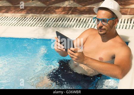 Jeune homme à l'aide de tablette tout en vous relaxant dans la piscine Banque D'Images