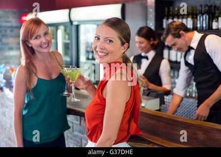 Portrait d'amis tenant un cocktail en face de comptoir bar Banque D'Images