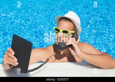 Guy ayant un appel Internet à partir de la piscine Banque D'Images
