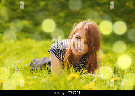 Red hair girl lying in grass Banque D'Images