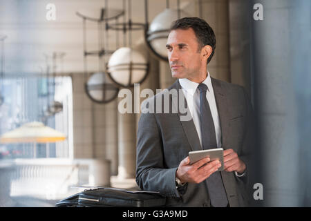 Homme d'entreprise with digital tablet looking away Banque D'Images