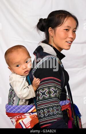 Une femme Hmong et son bébé, portant des costumes traditionnels de Sapa, province de Lao Cai, Vietnam Banque D'Images