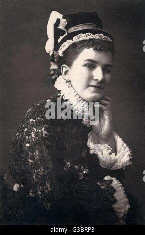 Une femme victorienne dans un chapeau et robe blanche à froufrous ruff et manchettes, peut-être une actrice en costume Banque D'Images
