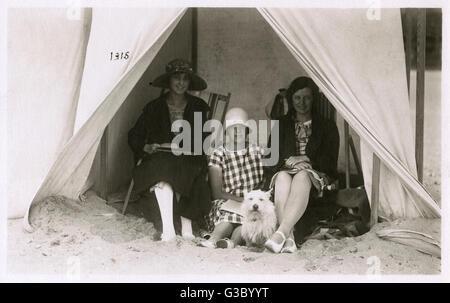 Trois jeunes femmes dans une tente sur la plage avec un chien de terrier blanc à leurs pieds. Date: vers 1930 Banque D'Images