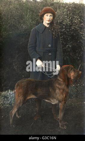 Jeune femme avec un chien Bloodhound dans un jardin. Date: vers 1930 Banque D'Images