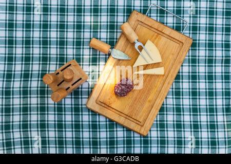La saucisse et le fromage sur une planche en bois à l'extérieur en été Banque D'Images