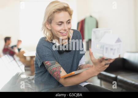 Souriante jeune femme tatouée architect holding model Banque D'Images