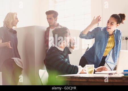 Des jeunes gens d'affaires high fiving in office Banque D'Images