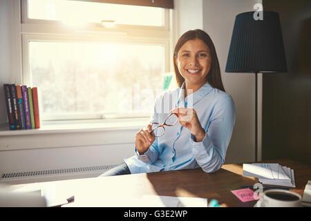 Ambiance business woman sitting at desk smiling at the camera tenant une paire de lunettes dans la main Banque D'Images