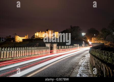 Des sentiers de lumière sur une route et bâtiment en arrière-plan éclairé à la nuit; Alnwick, Northumberland, Angleterre Banque D'Images