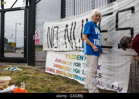 Burghfield, UK. 11 Juin, 2016. Ex-Greenham les militants de la paix commune accrocher des bannières sur la clôture Banque D'Images