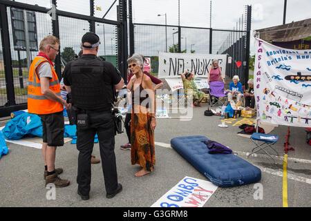 Burghfield, UK. 11 Juin, 2016. Un Ministère de la Défense policier débats avec les militants de la paix s'accrochant Banque D'Images