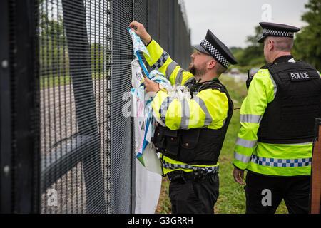 Burghfield, UK. 11 Juin, 2016. Ministère de la Défense policiers enlever une bannière accrochée par ex-Greenham Banque D'Images