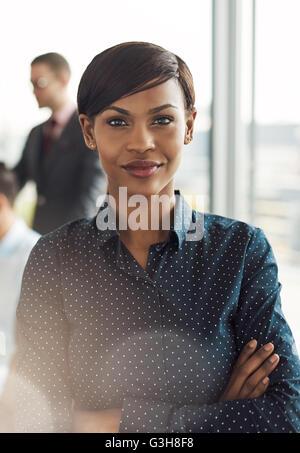Belle jeune souriant business woman in office avec chemisier à pois, bras croisés et confiant comme expression forte Banque D'Images