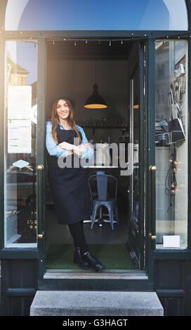 Seul mignon femelle barista en tablier et chapeau avec bras croisés appuyé contre porte dans cafe Banque D'Images