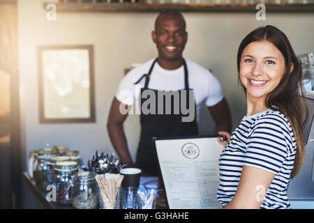 Belle jeune femme en chemise rayée à l'expression joyeuse menu près de young African holding coffee house propriétaire Banque D'Images