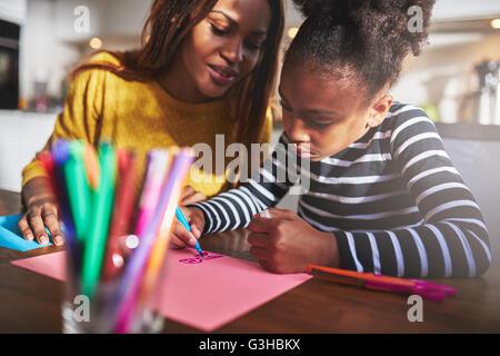 Maman et enfant dessin dans cuisine, mère et fille noire Banque D'Images