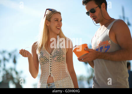 Couple strolling et manger du yogourt glacé à Venice Beach, Californie, USA Banque D'Images