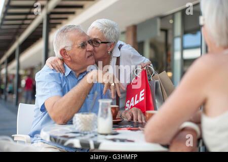 Femme shopper kissing senior man on cheek at sidewalk cafe Banque D'Images