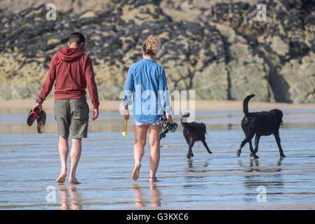 Un couple promènent leurs chiens sur la plage de Fistral, Newquay, Cornwall. Banque D'Images