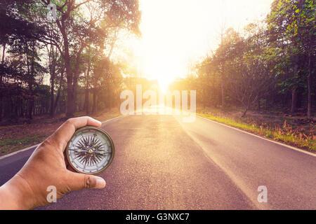 Hand holding compass sur route asphaltée vide et le coucher du soleil. Banque D'Images