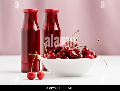 Les cerises dans un bol et deux bouteilles de jus de cerise. Focus sélectif. Banque D'Images