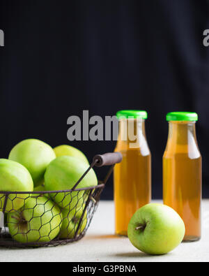 La pomme verte dans un panier et deux bouteilles de jus de pomme. Focus sélectif. Banque D'Images