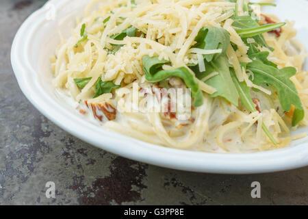 Les pâtes à la crème de tomates séchées au soleil, fromage, roquette et pesto de basilic frais Banque D'Images