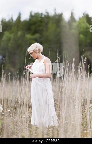 La Suède, Vastmanland, Teenage girl (16-17) in white dress standing in meadow parmi les plantes séchées